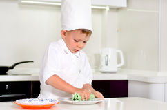 Cozinheiro chefe do rapaz pequeno que limpa suas placas ao cozinhar Imagens de Stock Royalty Free
