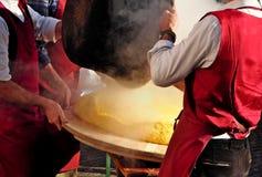 Cozinheiro chefe dois para derramar apenas feita e ainda cozinhar o Polenta na placa de corte de madeira redonda imagem de stock