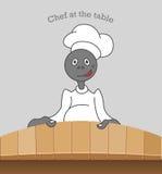 Cozinheiro chefe dos desenhos animados na mesa de cozinha cercada por dispositivos e por alimento de cozinha Imagens de Stock Royalty Free