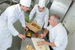 Cozinheiro chefe e assistentes que cortam legumes frescos para cozinhar fotografia de stock