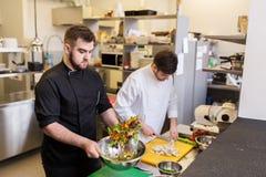 Cozinheiro chefe e cozinheiro que cozinham o alimento na cozinha do restaurante fotografia de stock royalty free