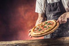 Cozinheiro chefe e pizza Pizza de oferecimento do cozinheiro chefe no hotel ou no restaurante fotografia de stock