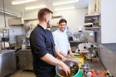 Cozinheiro chefe e cozinheiro que cozinham o alimento na cozinha do restaurante Foto de Stock