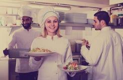 Cozinheiro chefe e seus assistentes que preparam a refeição fotos de stock