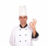 Cozinheiro chefe encantador do indivíduo que gesticula o sinal aprovado com dedos Foto de Stock