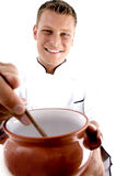 Cozinheiro chefe esperto que cozinha no potenciômetro da porcelana Fotografia de Stock Royalty Free