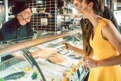Cozinheiro chefe experiente que toma um peixe fresco do congelador para cozinhá-lo fotos de stock