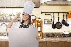 Cozinheiro chefe fêmea asiático feliz com o gesto aprovado que guarda a placa branca Fotografia de Stock