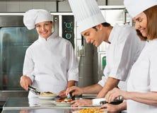 Cozinheiro chefe fêmea With Colleagues Working na cozinha Foto de Stock
