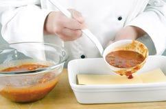 Cozinheiro chefe fêmea com molho de tomate em uma concha imagens de stock royalty free