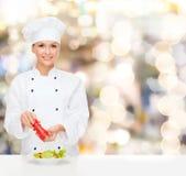 Cozinheiro chefe fêmea de sorriso que tempera a salada vegetal fotos de stock