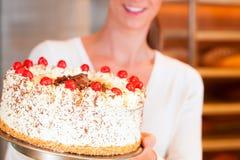 Cozinheiro chefe fêmea do padeiro ou de pastelaria com torte imagens de stock royalty free