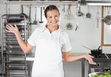Cozinheiro chefe fêmea Gesturing In Kitchen Foto de Stock