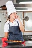 Cozinheiro chefe fêmea Licking Finger Fotografia de Stock Royalty Free
