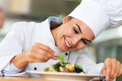 Cozinheiro chefe fêmea na cozinha fotos de stock