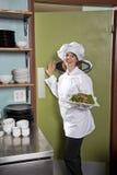 Cozinheiro chefe fêmea no restaurante com placa de salada imagem de stock royalty free