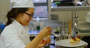 Cozinheiro chefe fêmea que decora queques na cozinha no restaurante 4k vídeos de arquivo