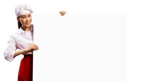 Cozinheiro chefe fêmea que guardara um cartaz para o texto Fotos de Stock