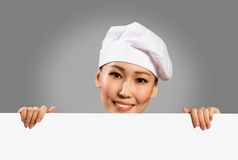 Cozinheiro chefe fêmea que guardara um cartaz para o texto imagem de stock