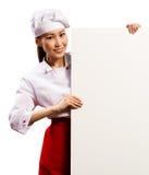 Cozinheiro chefe fêmea que guardara um cartaz para o texto imagens de stock