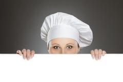 Cozinheiro chefe fêmea que olha sobre o quadro de avisos Imagens de Stock Royalty Free