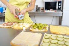 Cozinheiro chefe fêmea que prepara o sanduíche fotos de stock royalty free