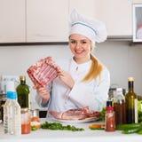 Cozinheiro chefe fêmea que trabalha com carne de cabras na cozinha Foto de Stock Royalty Free
