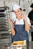 Cozinheiro chefe fêmea Showing Okay Sign na cozinha Imagens de Stock Royalty Free