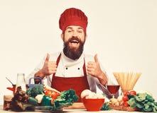 Cozinheiro chefe feliz que está sobre ingredientes e que mostra os polegares acima fotografia de stock