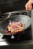 Cozinheiro chefe que cozinha vegetais no frigideira chinesa Fotografia de Stock