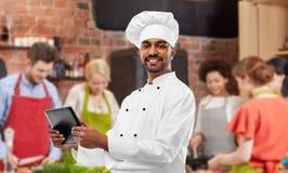 Cozinheiro chefe indiano masculino com o PC da tabuleta na aula de culinária imagens de stock royalty free