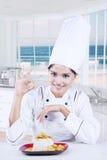 Cozinheiro chefe indiano que sorri com o prato na placa Fotografia de Stock