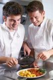 Cozinheiro chefe Instructing Male Trainee na cozinha do restaurante imagens de stock royalty free