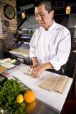 Cozinheiro chefe japonês no restaurante que faz o rolo de sushi Foto de Stock