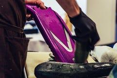 Cozinheiro chefe masculino Cutting Eggplant na cozinha - com a luva em sua mão, em conceito da pessoa de trabalho dura e na higie fotografia de stock
