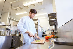 Cozinheiro chefe masculino feliz que cozinha o alimento na cozinha do restaurante Imagem de Stock Royalty Free