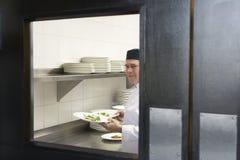 Cozinheiro chefe masculino With Food Plates na cozinha Foto de Stock