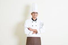 Cozinheiro chefe masculino indiano considerável no uniforme com ferramentas da cozinha Fotografia de Stock