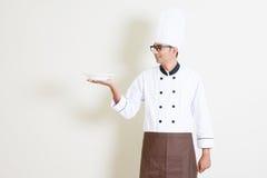 Cozinheiro chefe masculino indiano considerável no uniforme que guarda uma placa vazia Fotografia de Stock Royalty Free