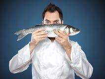 Cozinheiro chefe masculino novo com peixes do seabass Imagem de Stock Royalty Free