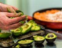 Cozinheiro chefe masculino Pealing Avocado para a refeição do casamento imagem de stock royalty free