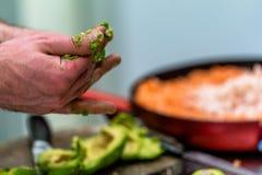 Cozinheiro chefe masculino Pealing Avocado para a refeição do casamento foto de stock