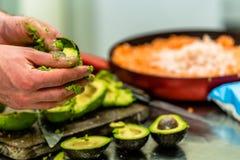 Cozinheiro chefe masculino Pealing Avocado para a refeição do casamento fotografia de stock