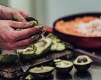 Cozinheiro chefe masculino Pealing Avocado para a refeição do casamento - a cozinha ajustou-se com ação, somente mãos do ` s do c foto de stock