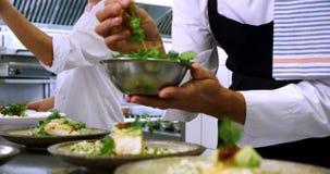 Cozinheiro chefe masculino que decora placas do aperitivo na estação 4k da ordem filme