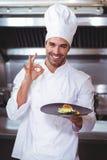 Cozinheiro chefe masculino que guarda a placa e que faz o sinal aprovado Imagem de Stock Royalty Free