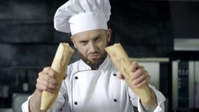 Cozinheiro chefe masculino que quebra o pão francês no movimento lento Mãos do close up que quebram o pão filme