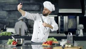 Cozinheiro chefe masculino que toma a foto do selfie na cozinha Cozinheiro chefe profissional com faca vídeos de arquivo