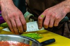 Cozinheiro chefe masculino Slicing Avocado para a refeição do casamento foto de stock