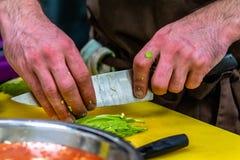 Cozinheiro chefe masculino Slicing Avocado para a refeição do casamento foto de stock royalty free